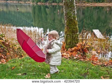 Joven niño manejando un gran paraguas al aire libre