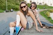picture of roller-derby  - happy young woman fastening the roller skates and is getting ready to ride outdoors - JPG