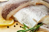 stock photo of hake  - Fillets of Raw Fish Hake with Lemon Black Peppercorn and Rosemary closeup on Cutting Board - JPG