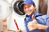 stock photo of pipefitter  - Portrait of a technician repairing a washing machine - JPG