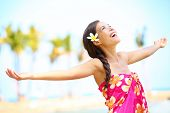 Free happy elated beach woman in freedom joy concept. Beautiful girl smiling with arms out looking u