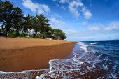 stock photo of negro  - Tropical beach with dark volcanic sand and blue sea with waves - JPG
