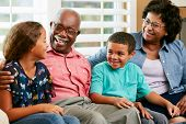 stock photo of 70-year-old  - Grandparents With Grandchildren Sitting On Sofa And Talking - JPG