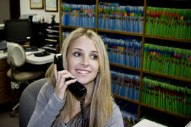 image of medical office  - A secretary smiles at the front desk of a medical or dental office - JPG