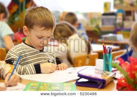 Niño dibuja en el jardín de la infancia