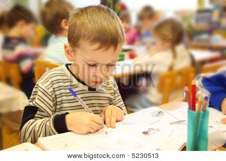 Niño de dibujo en el jardín de la infancia