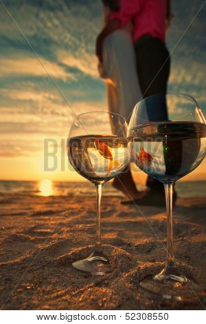 Reflection of holding bride and groom in wine glasses with golden fishes