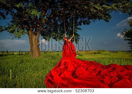 Beautiful woman in red dress with flower wreath on the swing in the forest in sunset