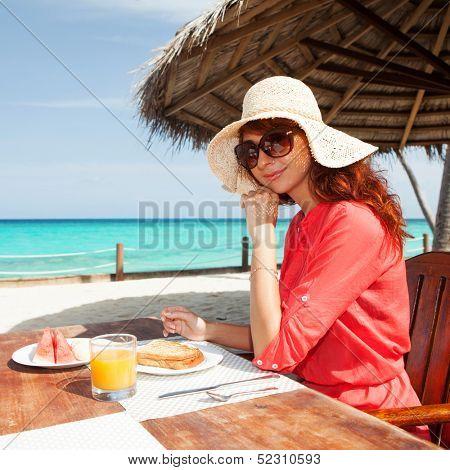 Fashion woman having breakfast on the beach