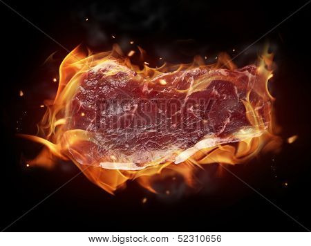 Concept of burning raw beef steak isolated on black background