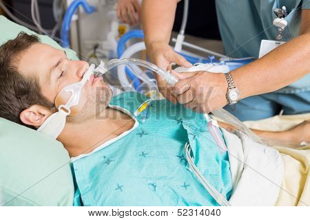 Nurse adjusting endotracheal tube in patient's mouth at hospital