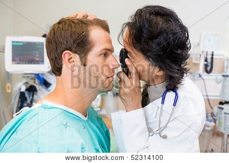 Doctor with ophthalmoscope examining patient's eye in hospital