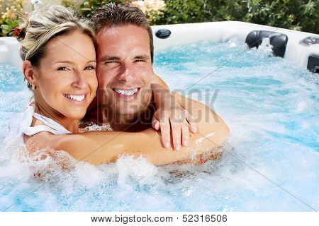 Happy couple relaxing in hot tub. Vacation.