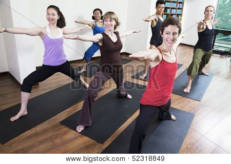 Group of people doing yoga during a yoga class