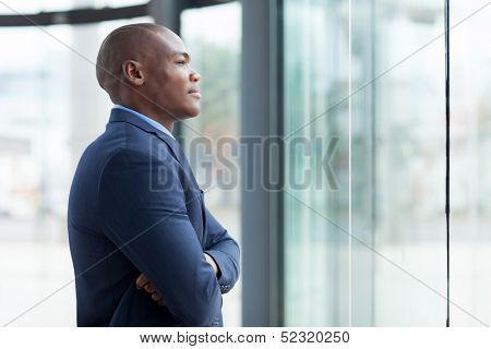 thoughtful african businessman with arms crossed in office