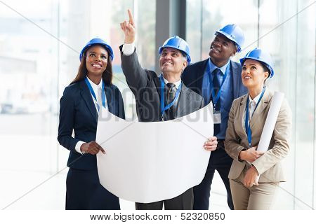 group of construction workers holding blue print and discussing project