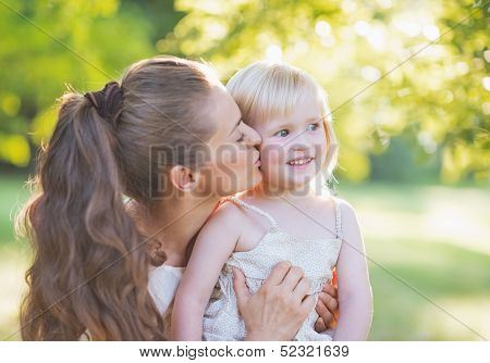 Portrait Of Mother Kissing Baby Outdoors