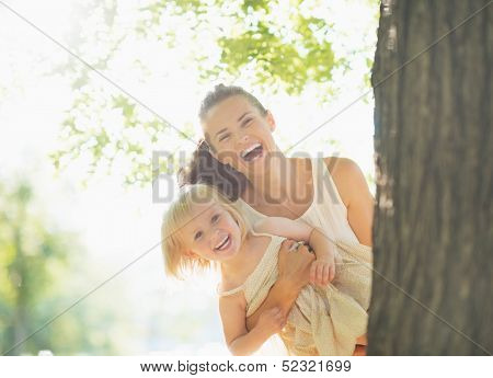 Happy Mother And Baby Looking Out From Tree