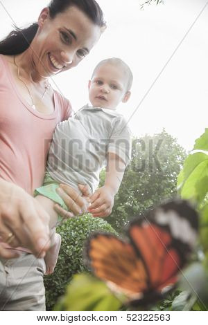 Smiling mother and son pointing and looking at a butterfly in the garden
