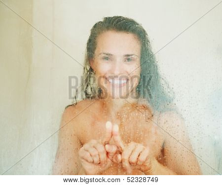 Happy Young Woman Drawing Heart In Weeping Glass Shower Door