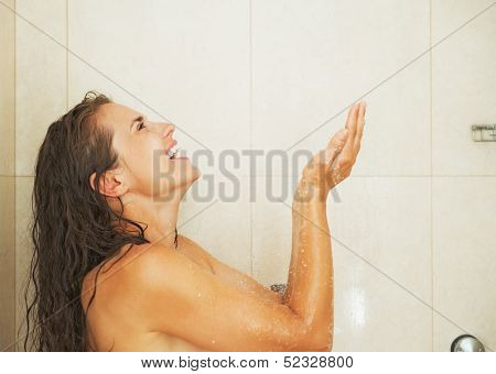 Smiling Young Woman Catching Water Drops In Shower
