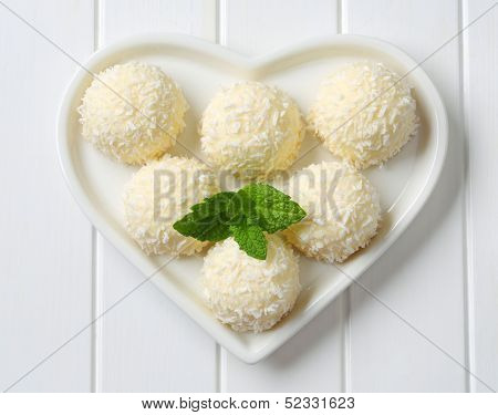 six white chocolate pralines with grated coconut and mint, on a heartshaped plate