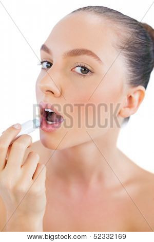 Pretty young model applying lip balm and looking at camera