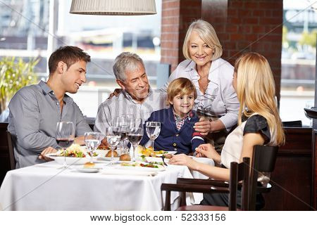 Happy family sitting in a restaurant and eating out