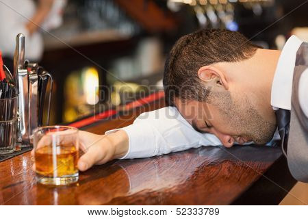 Drunk businessman lying on a counter in a classy bar