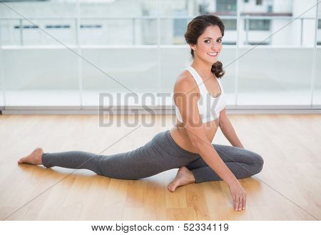Sporty cheery brunette stretching on the floor in bright room