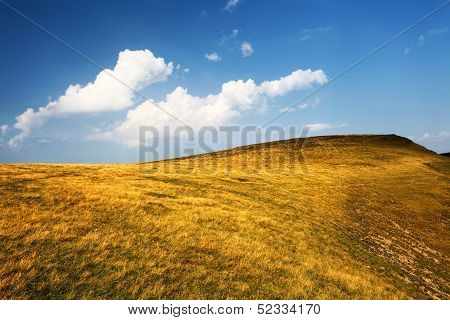 Hill With Dry Yellow Grass And Blue Sky