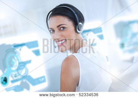 Pretty call center employee using futuristic holographic interface smiling at the camera in office