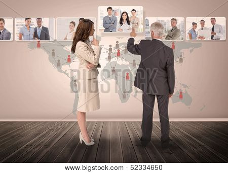 Business people selecting digital interface together showing coworkers