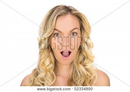 Surprised curly haired blonde posing on white background