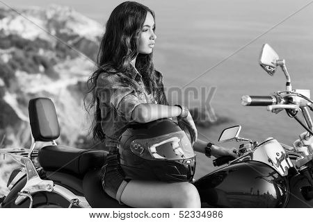 Biker girl sits on a motorcycle