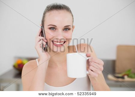Cheerful young woman making a phone call and holding a mug looking at camera in the kitchen at home