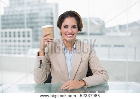 Smiling businesswoman holding disposable cup at her desk in bright office