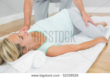 Physiotherapist checking patients hips on a mat on the floor in bright room