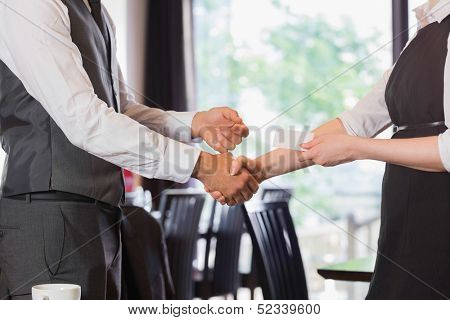 Business team shaking hands and swapping card in a cafe