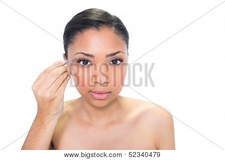 Concentrated young dark haired model plucking her eyebrows on white background