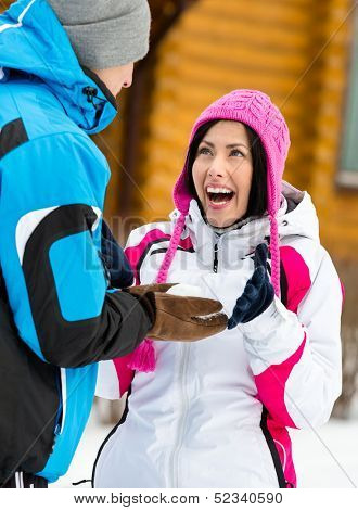 Couple having fun outdoors during winter holidays and playing at snowballs