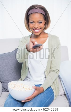 Cheerful cute woman sitting on sofa changing tv channel and holding popcorn in bright living room
