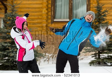 Happy couple having fun outdoors during winter vacations and playing at snowballs