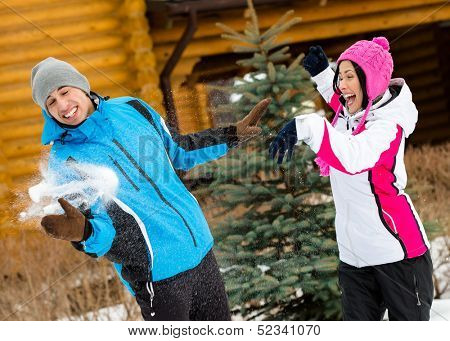 Cute couple having fun outdoors during winter vacations and playing at snowballs