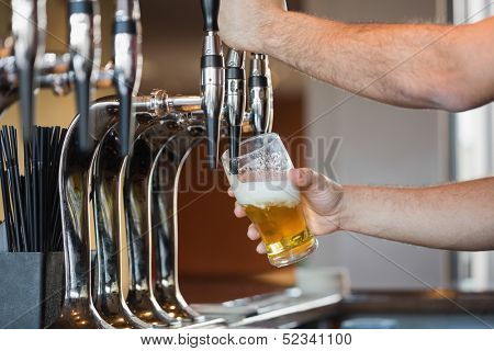 Barman's arms pulling a pint of beer behind the bar