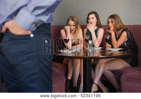 Three friends checking out mans rear in a nightclub