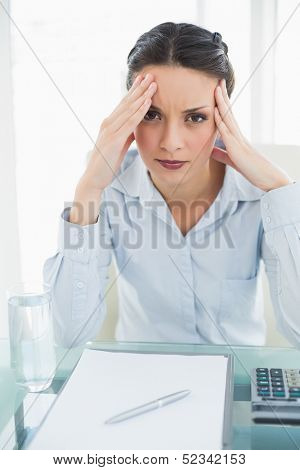 Troubled stylish brunette businesswoman holding her head and looking at camera in bright office