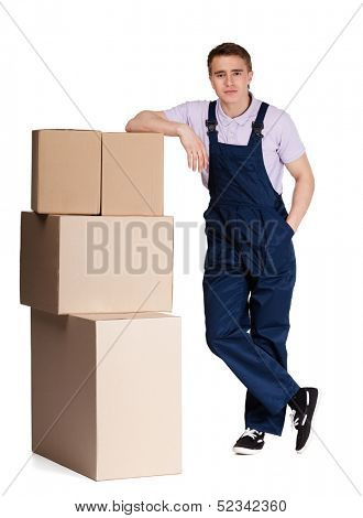 Young delivery man in overalls with pasteboard boxes, isolated on white. Transportation service