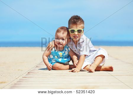 Portrait of kids resting on the beach in summer