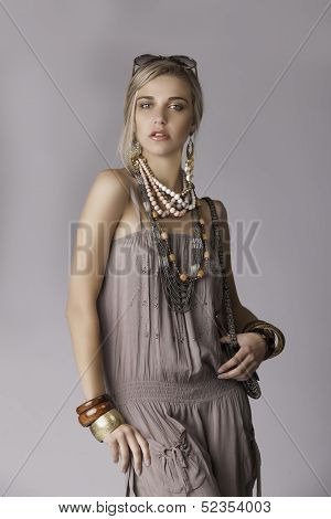 Portrait of beautiful blonde in safari outfit with tribal accessories
